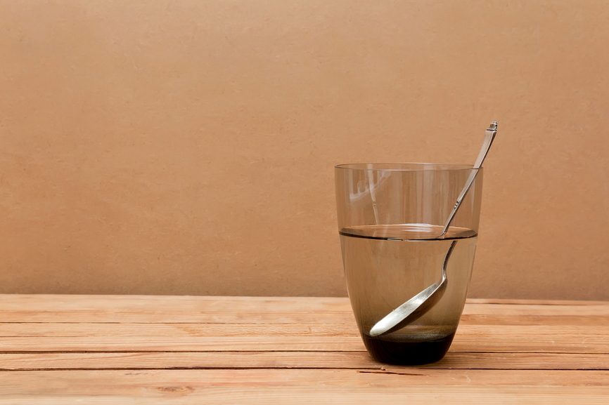 Glass of water and spoon on wooden table.